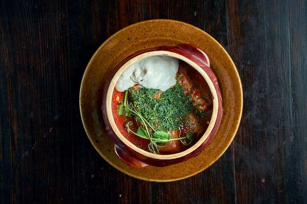 Tradycyjne ukraińskie danie to gołąbki z mielonym mięsem i ryżem w misce z czerwonym sosem i kwaśną śmietaną.