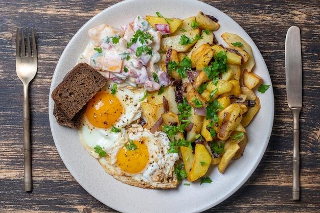 Tradycyjne ukraińskie jedzenie, smażone ziemniaki z cebulą, jajka sadzone, sałatka jarzynowa, czarny chleb na podłoże drewniane, zbliżenie, widok z góry