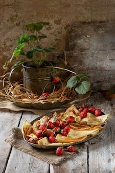 Tradycyjne ukraińskie lub rosyjskie naleśniki z jagodami truskawek i miodem na drewnianym stole