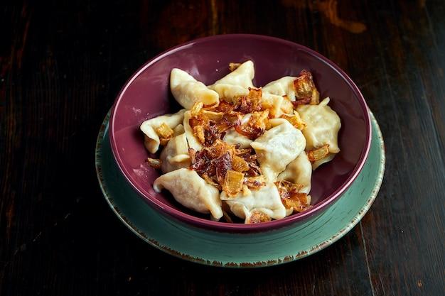 Tradycyjne ukraińskie pierogi z mięsem mielonym i smażoną cebulą, podawane w czerwonej misce na czarnym tle. zamknij widok na pierogi lub varenyky