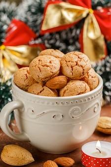 Tradycyjne włoskie ciasteczka migdałowe w lekkiej filiżance. ciastka amaretti. boże narodzenie i nowy rok