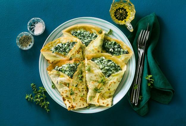 Tradycyjne włoskie naleśniki ze szpinakiem i ricottą na niebieskim stole. zdrowa dieta wegetariańska