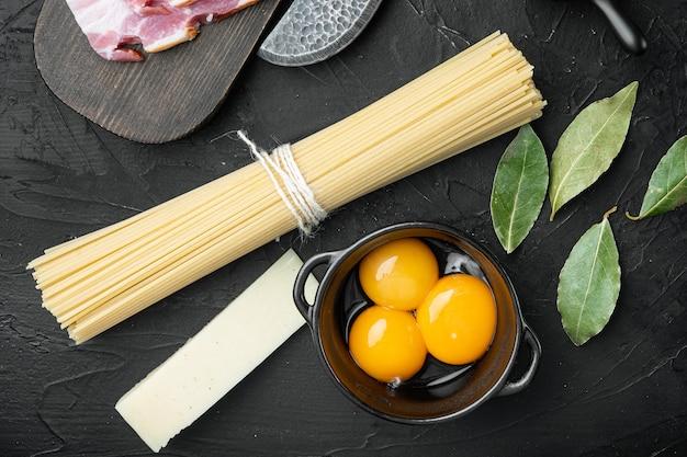 Tradycyjne włoskie składniki makaronu carbonara. bekon, spaghetti, parmezan i pecorino, jajko, zestaw czosnku, na czarnym kamiennym tle, widok z góry płasko leżący