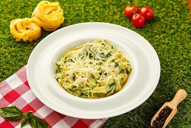 Tradycyjne włoskie tagliatelle z makaronem ze szpinakiem, twardym parmezanem i sosem śmietanowym