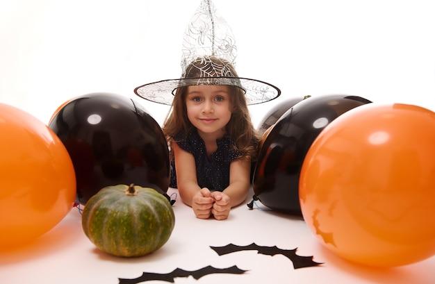 Tradycyjne wydarzenie, koncepcja halloween party. piękna mała czarownica dziewczyna w magicznym kapeluszu leżącego na białym tle z miejsca na kopię obok czarnych ręcznie robionych nietoperzy filcowych, dyni i pomarańczowych czarnych balonów