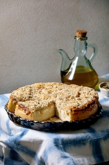 Tradycyjne wypiekane ciasto chlebowe z cebulą, ziołami i serem w naczyniu ceramicznym podane na niebieskim i białym obrusie