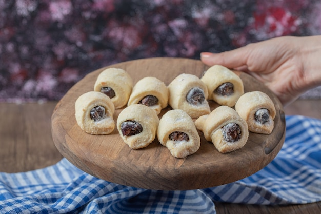Tradycyjne zawijane ciasteczka z konfiturą truskawkową na drewnianej desce.