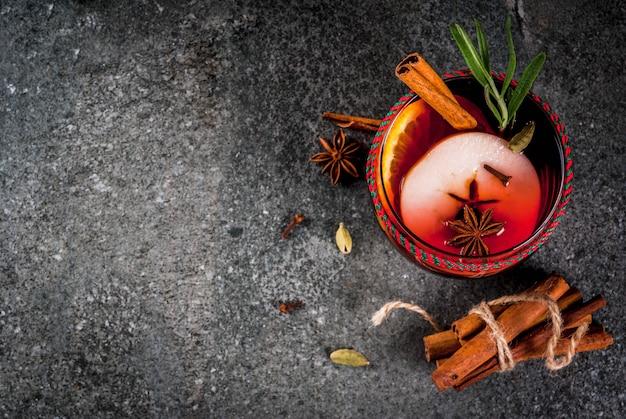 Tradycyjne zimowe i jesienne napoje. koktajle świąteczne i święto dziękczynienia. grzane wino z pomarańczą, jabłkiem, rozmarynem, cynamonem i przyprawami na ciemnym kamieniu, copyspace widok z góry