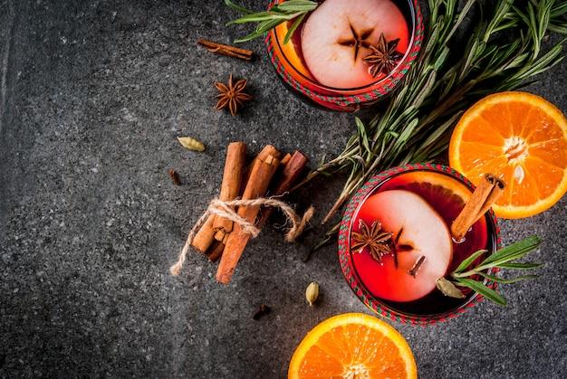 Tradycyjne zimowe i jesienne napoje. koktajle świąteczne i święto dziękczynienia. grzane wino z pomarańczą, jabłkiem, rozmarynem, cynamonem i przyprawami na ciemnym kamieniu, widok z góry