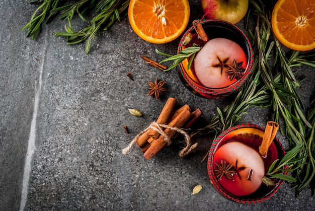 Tradycyjne zimowe i jesienne napoje. koktajle świąteczne i święto dziękczynienia. grzane wino z pomarańczą, jabłkiem, rozmarynem, cynamonem i przyprawami