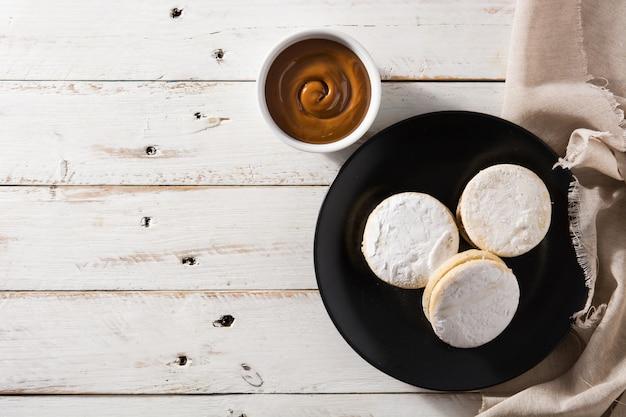 Tradycyjni argentyńscy alfajores z dulce de leche i cukierem na drewnianym stole, kopii przestrzeń
