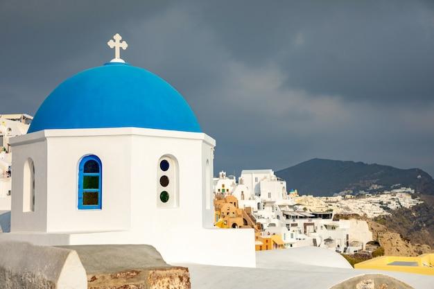 Tradycyjni i sławni domy i kościół z błękitnymi kopułami w oia, santorini, grecja