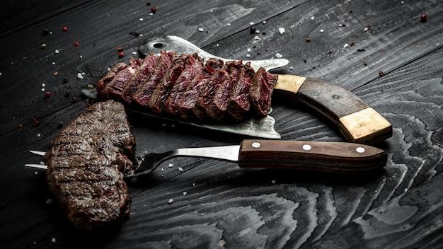 Tradycyjny amerykański grill suchy stek starzejący się rumsztyk z plastrami na pokładzie rzeźnika i widelcem. baner, miejsce przepis menu na tekst, widok z góry.