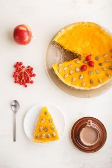 Tradycyjny amerykański słodki dyniowy kulebiak dekorujący głogowymi czerwonymi jagodami i dyniowymi ziarnami z filiżanką kawy na białym drewnianym tle. widok z góry.