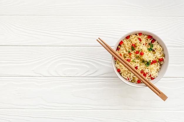 Tradycyjny azjatycki makaron jajeczny instant w talerzu pałeczkami