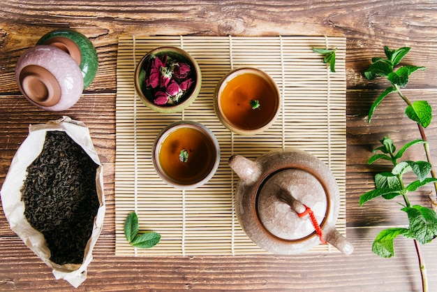 Tradycyjny azjatycki układ ceremonii parzenia herbaty z płatkami róż i gałązką mięty na drewnianym biurku