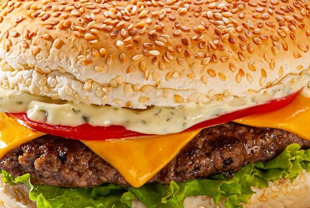 Tradycyjny brazylijski burger z pieczywem, serem topionym, sałatą, pomidorem, majonezem na białym tle.