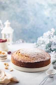 Tradycyjny budyń świąteczny z owocami i orzechami z jasnymi dekoracjami świątecznymi