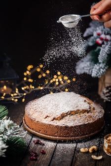 Tradycyjny budyń świąteczny z owocami i orzechami z ozdobami świątecznymi ciemnym tłem