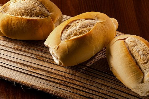 """Tradycyjny chleb brazylijski, spożywany codziennie, """"chleb francuski"""", na słomianej macie na brązowym drewnianym stole"""