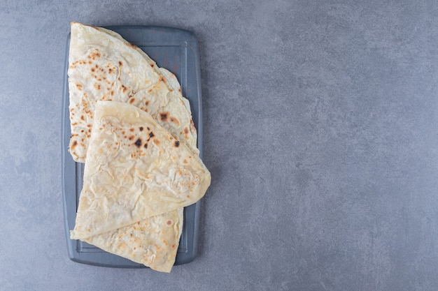 Tradycyjny chleb pszenny lavash na drewnianej tacy na marmurowym stole.