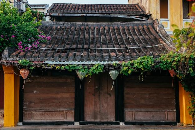 Tradycyjny dom z brązowymi drzwiami i chińskimi lampionami na starym mieście w hoi. miejsce światowego dziedzictwa. wietnam