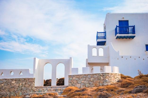 Tradycyjny dom z niebieskimi drzwiami i oknami na mykonos, grecja.