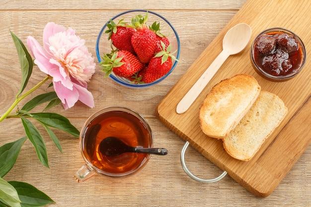 Tradycyjny domowy dżem truskawkowy w szklanej misce, świeże jagody, grzanki na desce do krojenia z łyżką, filiżanką herbaty i kwiatem piwonii na drewnianym biurku. widok z góry.