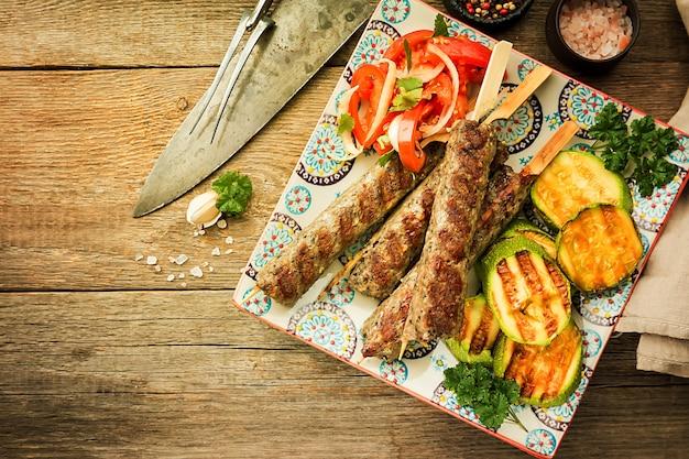Tradycyjny domowy grillowany turecki kebab adana urfa, kebab z mięsa mielonego, na talerzu z sałatką pomidorową i cukinią na drewnianym tle, widok z góry