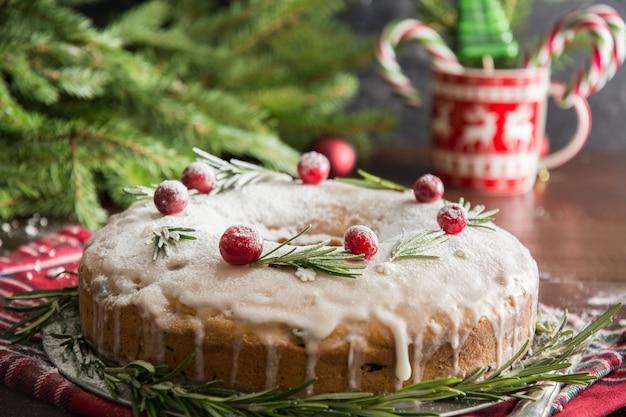 Tradycyjny domowy tort świąteczny z dekorowaną żurawiną i rozmarynem na ozdobnym talerzu.