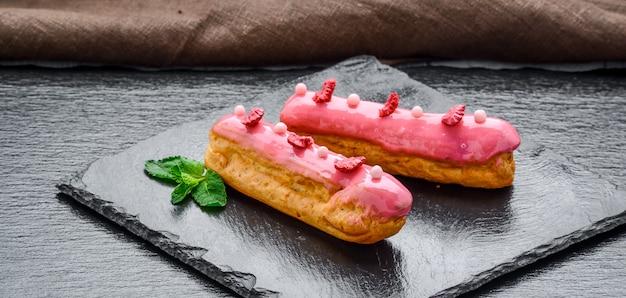 Tradycyjny francuski deser. eclair z polewą czekoladową i malinami.