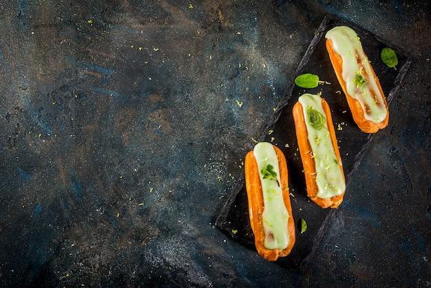 Tradycyjny francuski deser. mojito eclairs z skórką limonki i liśćmi mięty, na ciemnoniebieskim, widok z góry copyspace