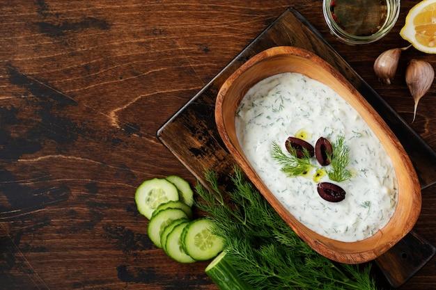 Tradycyjny grecki sos tzatziki w drewnianej misce z oliwek na starej rustykalnej powierzchni. widok z góry