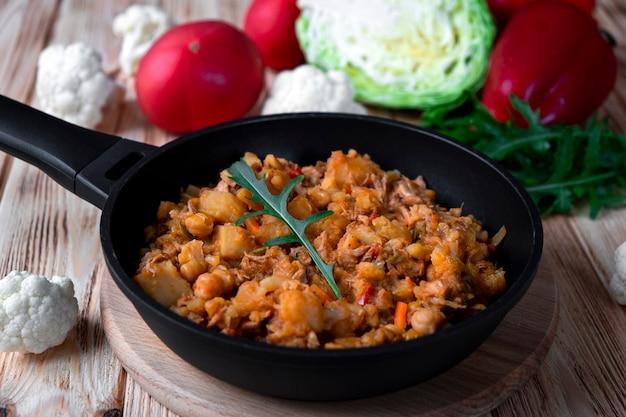 Tradycyjny gulasz z warzywami, ziemniakami, kapustą, cebulą, marchewką, kalafiorem, papryką z sosem pomidorowym, czosnkiem i ziołami w naczyniu do smażenia na drewnianym stole. rustykalne jedzenie na drewnianym tle