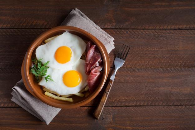 Tradycyjny hiszpański obiad - jajka sadzone z frytkami, peklowane plasterki wieprzowiny jamon. skopiuj miejsce na tekst