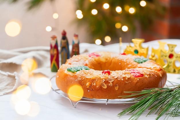 Tradycyjny hiszpański tort trzech króli, roscon de reyes z trzema królami, koroną, świątecznymi dekoracjami i lampkami bożonarodzeniowymi