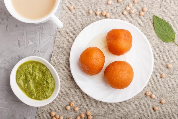Tradycyjny indyjski gulab jamun w białej płytce z miętowym chutney. widok z góry.