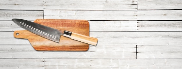 Tradycyjny japoński nóż szefa gyuto na desce do krojenia. biały drewniany baner w tle