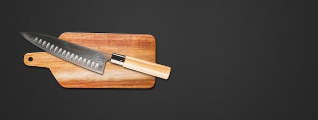 Tradycyjny japoński nóż szefa gyuto na desce do krojenia. czarne tło transparentu