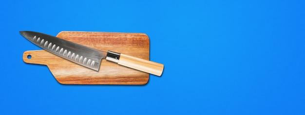 Tradycyjny japoński nóż szefa gyuto na desce do krojenia. niebieskie tło transparentu