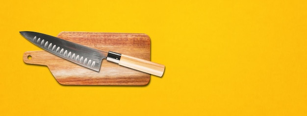 Tradycyjny japoński nóż szefa gyuto na desce do krojenia. żółte tło transparentu