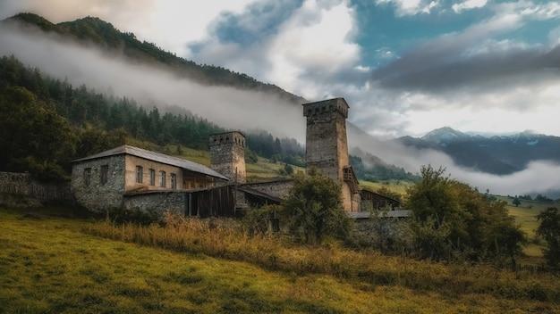 Tradycyjny kamienny dom z wieżą w górach swanetia gruzja rano w mglistej mgle w porannych górach