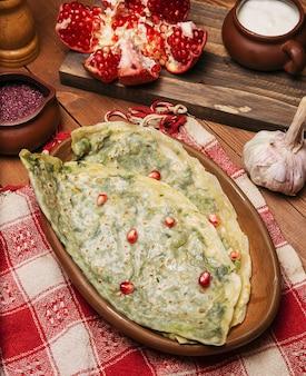 Tradycyjny kaukaski gutab warzywny, kutab, gozleme z sumakiem, nasiona granatu i jogurt w drewnianej tablicy