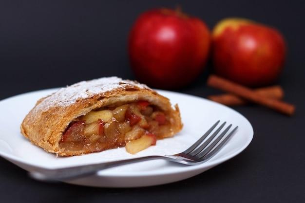 Tradycyjny kawałek strudla jabłkowego z cynamonem i cukrem pudrem