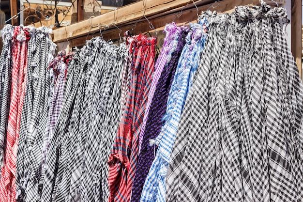 Tradycyjny keffiyeh lub kefia obwieszenie na wieszakach na bazarze w egipt
