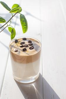 Tradycyjny koreański napój dalgona kawa w szklance z ziaren kawy na białej tablicy
