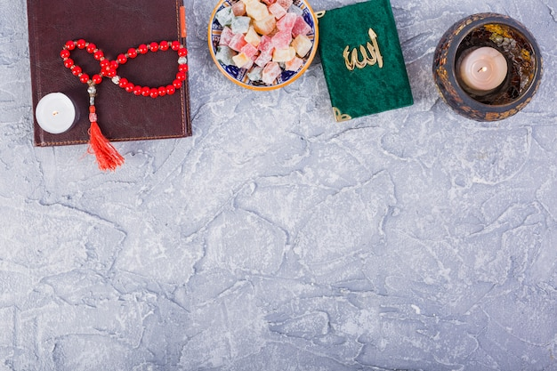 Tradycyjny kuran; różańce; zapalona świeca z wieloma rakhat-lukum na betonowym tle