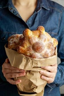 """Tradycyjny meksykański chleb zmarłych """"pan de muerto"""" w rękach młodych kobiet, niebieskie tło"""