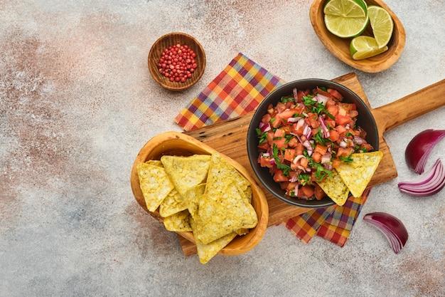 Tradycyjny meksykański sos pomidorowy salsa z nachos i składniki pomidory, chile, czosnek, cebula na jasnym tle łupka. pojęcie żywności ameryki łacińskiej i meksyku. makieta.