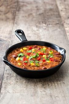 Tradycyjny meksykański tex mex chili con carne w smaży niecce na drewnianym stole
